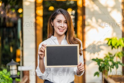 Asian partner Small business owner hands holding and showing the chalkboard