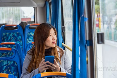 Asian Woman sitting  in the bus and using mobile phone when traveling around Dukezong ancient