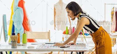 Young Asian designer woman working with computer and choosing multicolor chart at workplace
