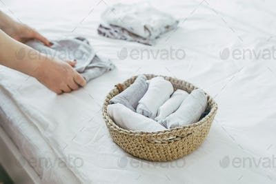 Woman folding clothes in jute basket in the konmari system. Concept of organizing minimalism clothes