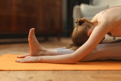 fitness female doing gymnastic bow, touches the knees with forehead