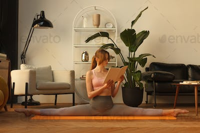 fitness female sitting in gymnastic split and reading book at home interior