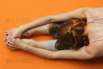 fitness female doing gymnastic bow, touches the knees with forehead on orange yoga mat