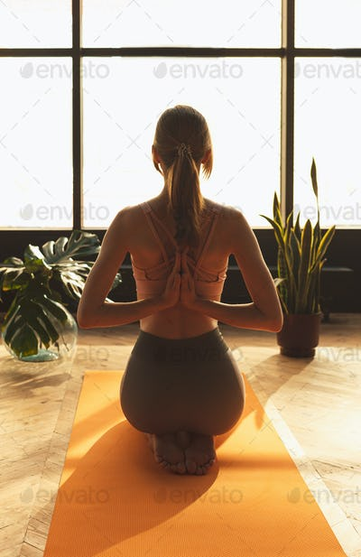 fitness girl doing yoga in lotus pose in home loft interior with many plants