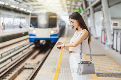 Young Asian woman passenger listening music via smart mobile phone and looking train