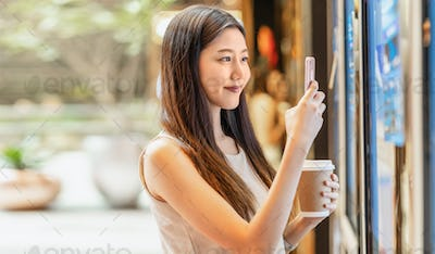 Asian young woman hand using smart mobile phone scanning the movie tickets machine for buy