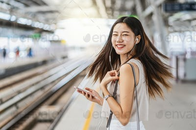 Young Asian woman passenger listening music via smart mobile phone with happiness action