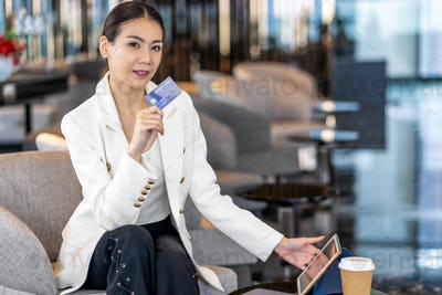Portrait Asian woman using credit card with technology tablet for online shopping in modern lobby