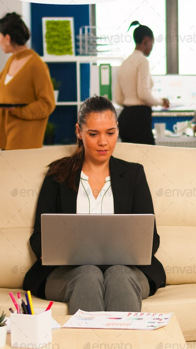 Manager woman holding laptop, looking on internet while sitting on couch smiling