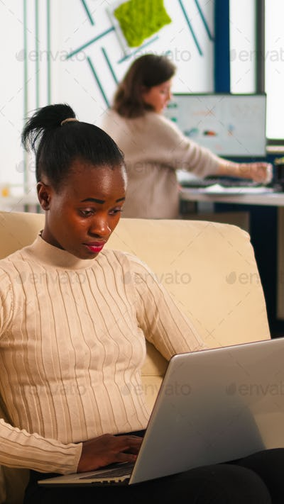Concentrated african business woman answering emails typing on laptop