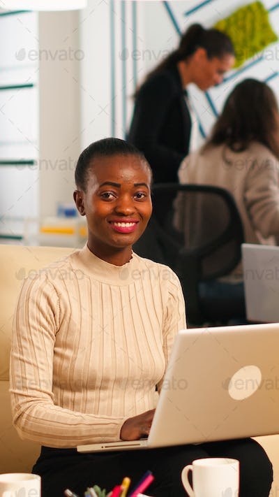 Portrait of african woman typing on laptop looking at camera smiling