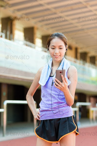 Woman listen to music with cellphone in sport arena