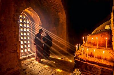 Two asian Burmish monk change the robe with sun ray in pagoda at bagan, mandalay, myanmar