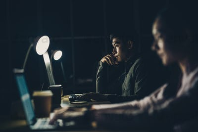 Asian businesswoman and businessman working hard late together with technology computer in office