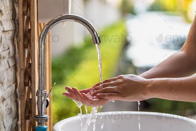 Closeup hands washing with Chrome faucet and soap for Coronavirus pandemic prevention