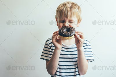 Child boy closed his eyes and laughs with a chocolate donut in his hands