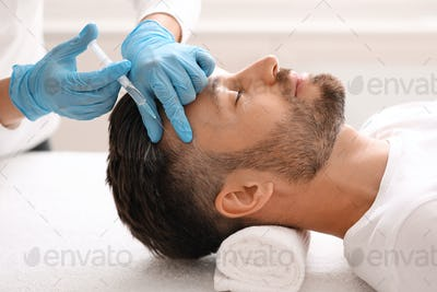 Middle-aged man having hair treatment at beauty salon