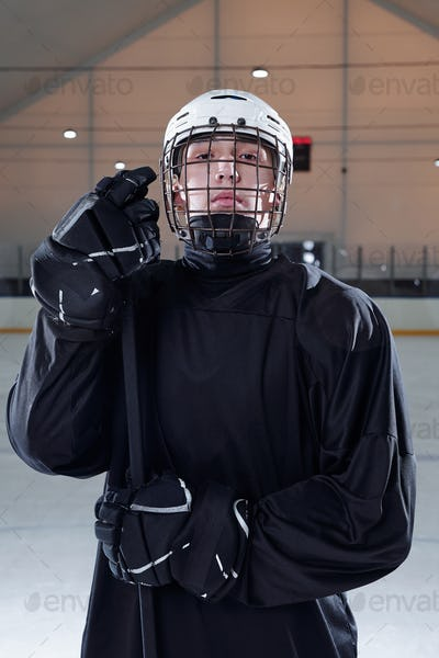 Professional hockey player in black sports uniform standing on rink after play