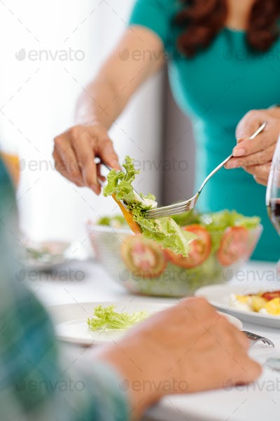 Housewife serving healthy salad