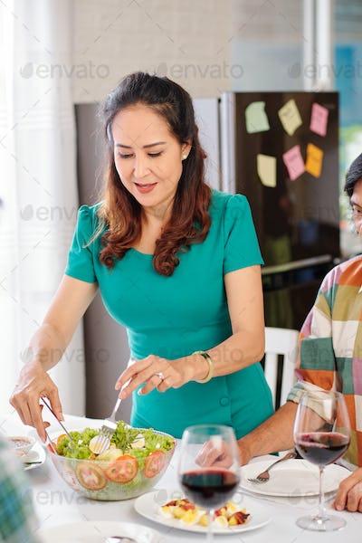 Woman serving vegetable salad