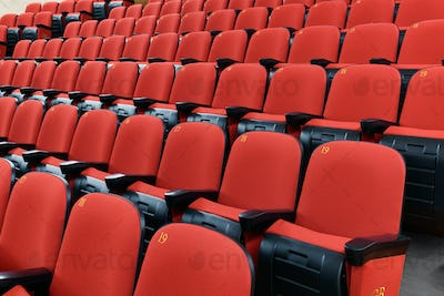 Rows of red chairs in a theatre auditorium