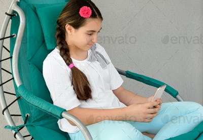 Young girl texting a message on her mobile