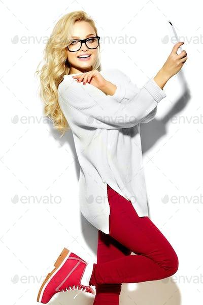 Portrait of cute blond woman posing in studio near white wall