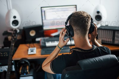 Listening to the music. Sound engineer in headphones working and mixing indoors in the studio