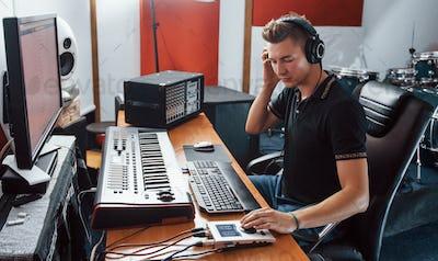 Sound engineer in headphones working and mixing music indoors in the studio