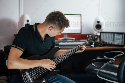 Young musician records bass guitar indoors in the studio