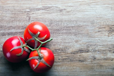 Fresh ripe tomatoes on wooden board background, copy space