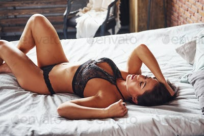 Beautiful sexy brunette woman is on the bed at morning time