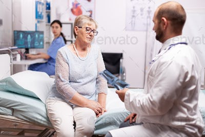 Surgeon discussing about treatment with senior woman