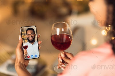 Black couple having online date, drinking red wine