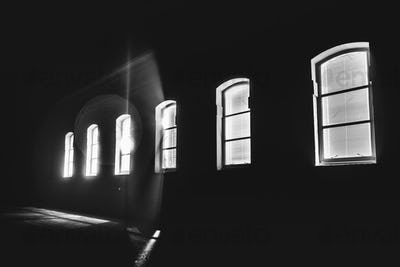 Bright light shinning through a row of windows in the middle of the night; black and white
