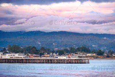 Evening view of the Santa Cruz wharf and shoreline; storm clouds cover the Santa Cruz mountains
