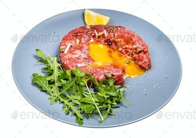 served Steak tartare on blue plate isolated