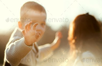 Child waving hand, boy with mother outdoor