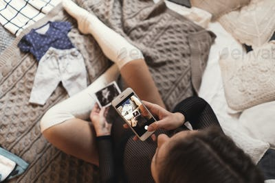 Pregnant young woman taking pictures of ultrasound photos with smartphone while relaxing on a bed