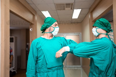 two surgeon doctor greeting with elbow bump
