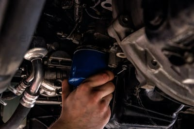 Car mechanic replaces oil filter on Service station