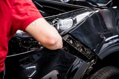 Car mechanic replaces car bumper on Service station