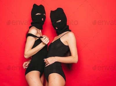 Portrait of two hot women posing in studio