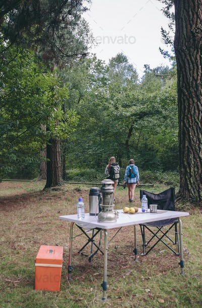 Women hiking with camping table in foreground