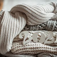 Christmas composition with wooden number 2021 on knitted items background.