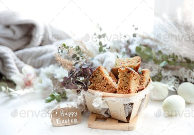 Happy Easter composition with pieces of Easter cake in a decorative basket.