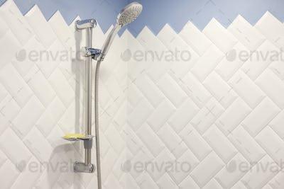 Modern shower on wall rail in modern white bathroom