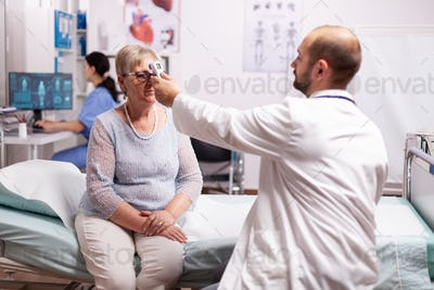 Worried doctor taking body temperature of senior woman