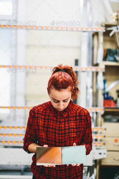 Woman glazier worker sticking together glass panes
