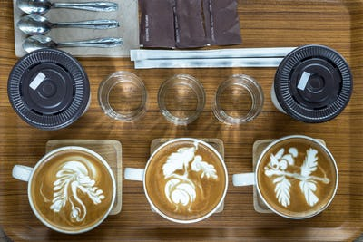 Top view of coffee cup set which consist of latte art, capuchino, glassed of water,